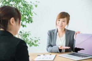 パソコンの画面を見せる女性と話を聞く女性