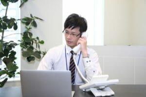 電話しながらパソコンを眺める男性